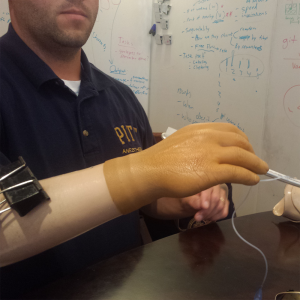 Shows Mr. Fagden holding a medical devices with his myoelectric prosthetic hand. The hand has a binder clip attached to it to assist him in holding objects.