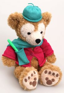 A teddy bear wearing a knit hat, scarf (with pocket) and sweater