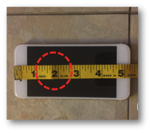 A ruler used to measure a phone is slightly bent, introducing error.