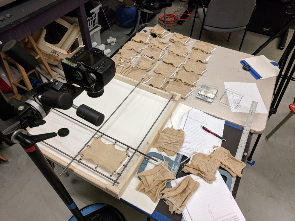 A photograph of the table with our data measurement setup, along with piles of patches that are about to be measured and have recently been measured. One patch is attached to the rods and clips used for stretching.